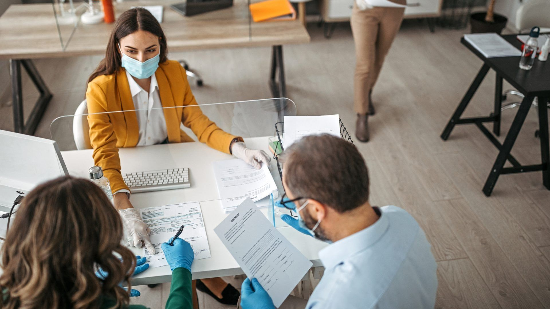 Couple signing a document on a meeting at insurance agent office wearing protective gloves and face mask.