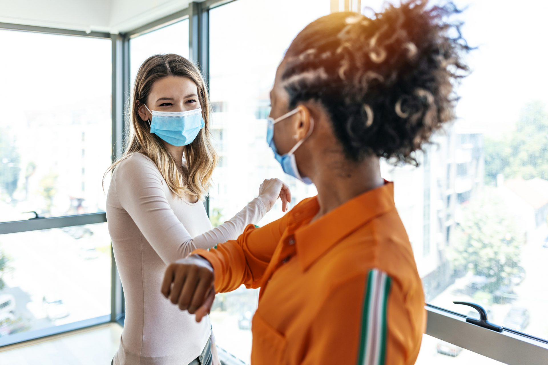 Two colleagues in medical masks avoiding  handshake when meeting in the office, greeting with bumping elbows during corona virus COVID-19 epidemic in office, Social distancing concept.