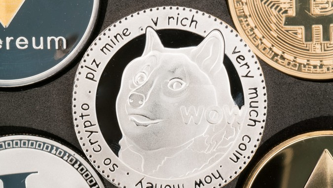 Dogecoin cryptocurrency real silver coin in middle of other crypto.