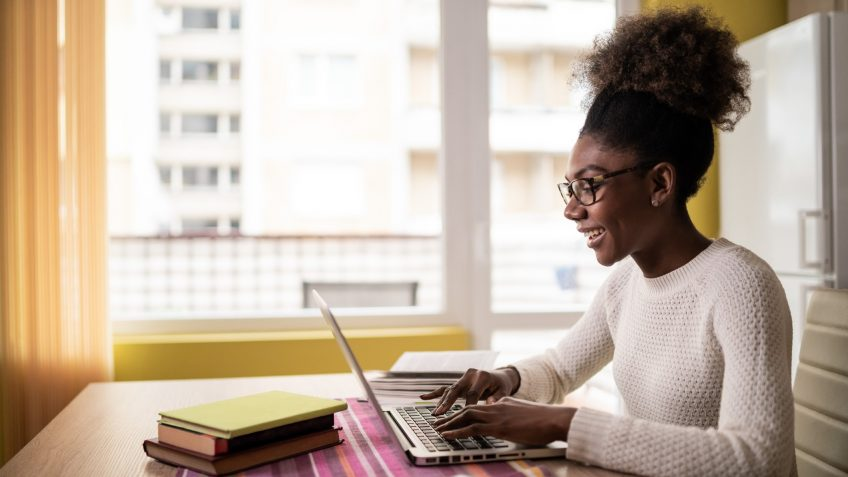 Afro Woman sitting at home and studying.