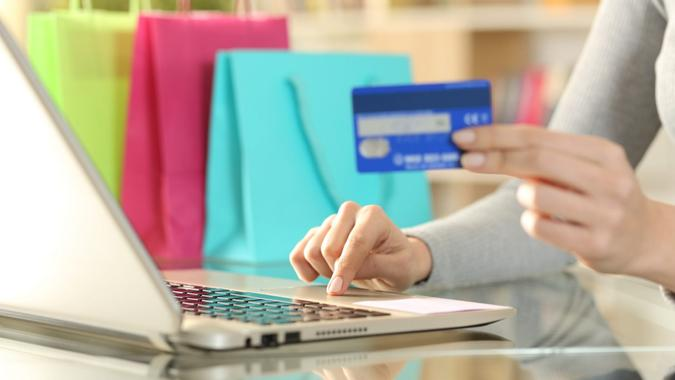 Shopper hands buying with credit card on laptop.