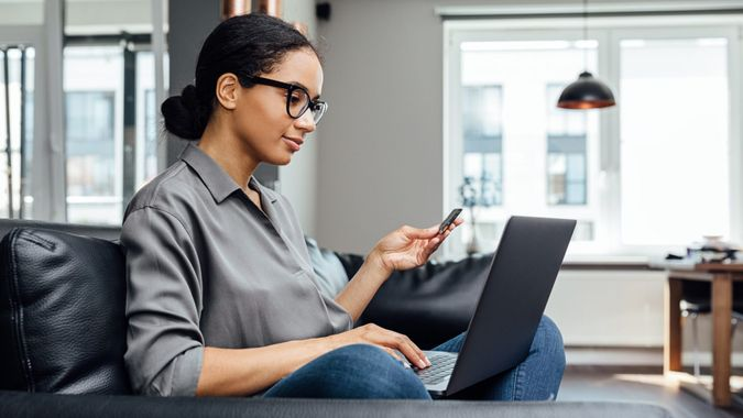 Young woman making online payment while sitting in the living room on sofa.