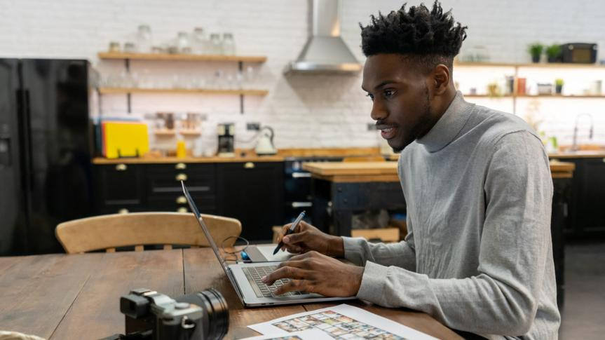 African American freelance photographer editing photos at home using a laptop computer and a pen tablet.