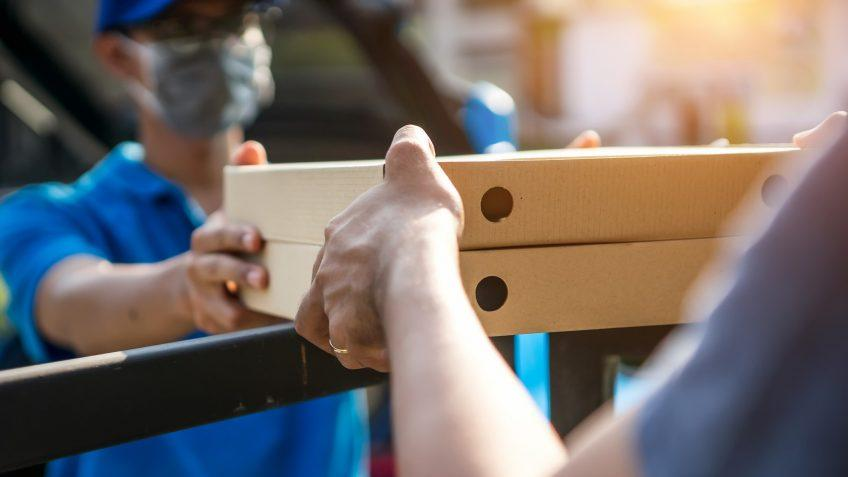 Asian delivery man wearing mask delivers pizza, customer in medical gloves signs on tablet.