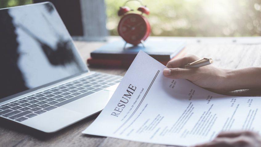 Business man review his resume application on desk, laptop computer, job seeker.