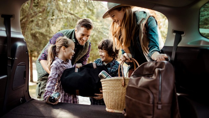 Close up of a young family packing up for a road trip.