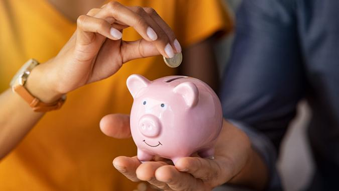 Close up of man holding pink piggybank while woman putting coin in it.