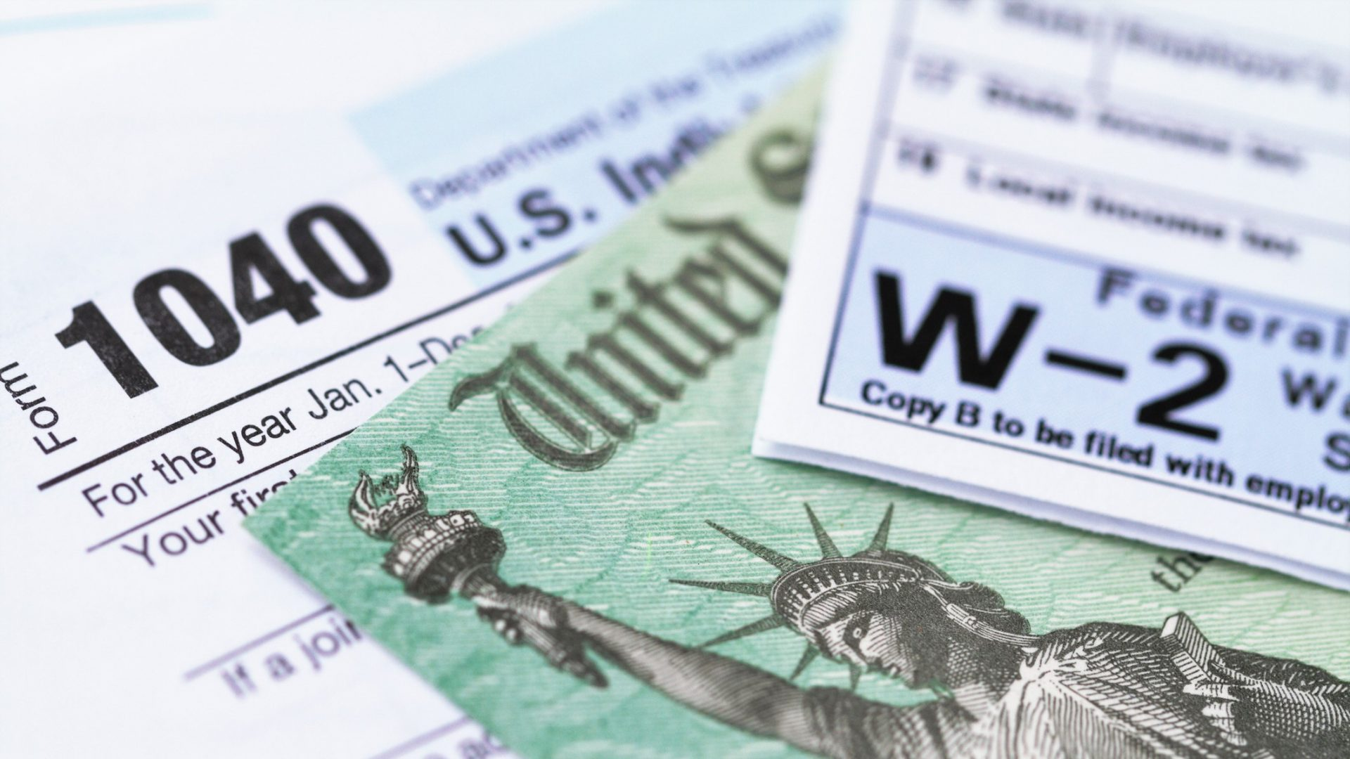 1040 income tax form and w-2 wage statement with a federal Treasury refund check.