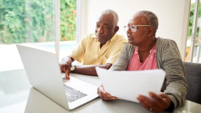 Shot of a senior african couple with a paper looking at a laptop at home.