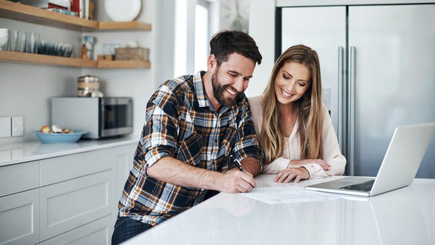 Shot of a young couple using a laptop and going through paperwork at home.