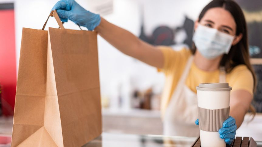 Young woman wearing face mask while serving takeaway breakfast and coffee inside cafeteria restaurant - Worker preparing delivery food inside bakery bar during coronavirus period - Focus on right hand.