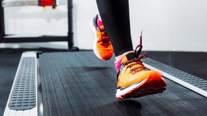 Close up of a person jogging on a treadmill in fitness center.