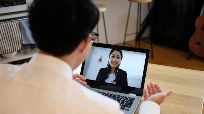 Asian businessman talking to colleague on web meeting.