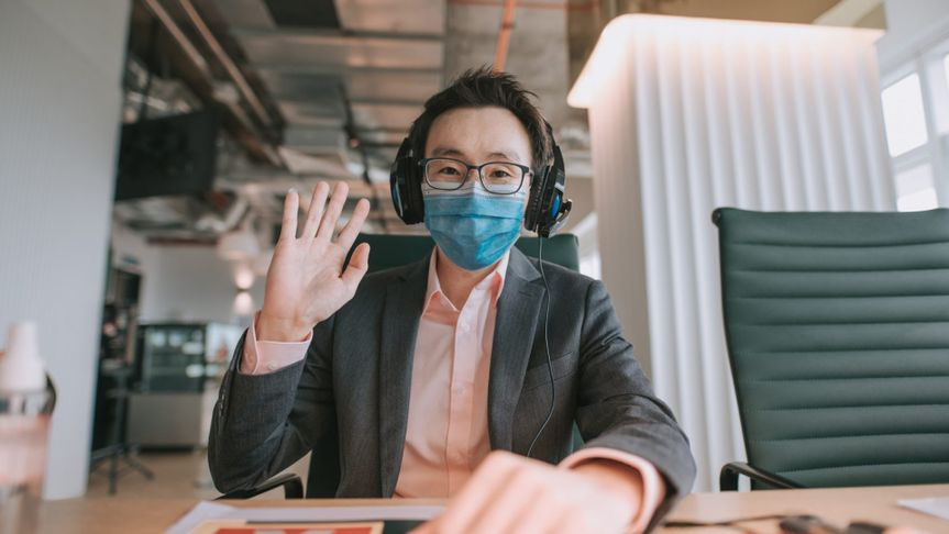 an asian chinese mid adult white collar worker talking to the camera video calling video conference with his business partners.