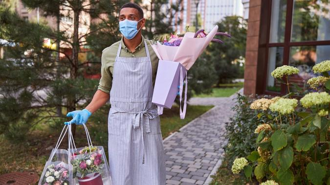 Florist in a mask walking outdoors while carrying plastic bags with flower pots and a paper package with bouquet.