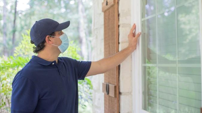 Repairmen, building inspectors, exterminators, engineers, insurance adjusters, or other blue collar workers examine a building/home's exterior walls.