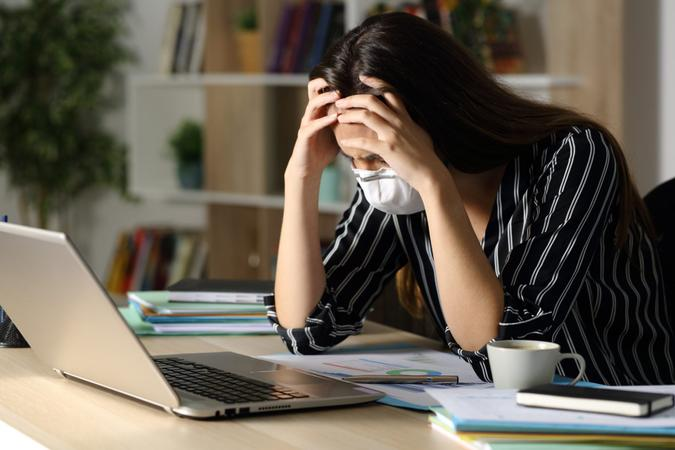 Sad teleworker woman wearing mask with problems due coronavirus sitting on a desk with laptop in the night at home office.