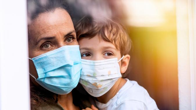 Caucasian Mature woman posing with her son, both with protective masks, very sad looking through window worried about loss of her job due Covid-19 pandemic.