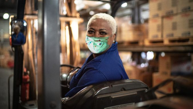Portrait of female worker driving forklift in warehouse.