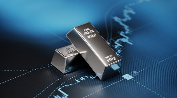 Silver bars sitting on blue graph.