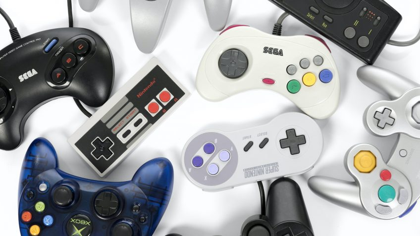 Taipei, Taiwan - February 19, 2018: A collection of retro video game controllers shot from above on a white background.