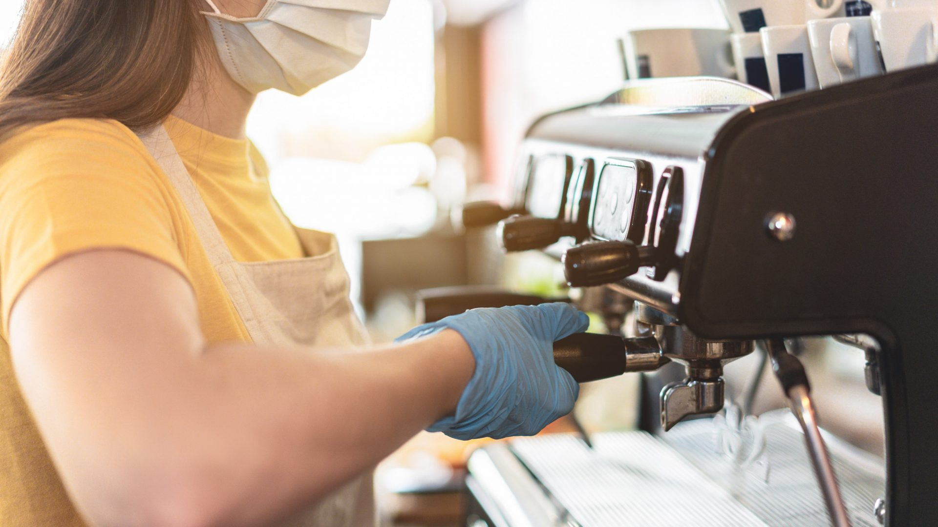 Young female working inside cafeteria bakery while making coffee wearing gloves and face mask for coronavirus spread prevention - Protective measures at work during Covid-19 outbreak - Focus on hand.