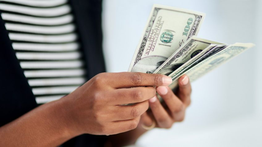 Cropped shot of an unrecognizable businesswoman counting money inside her office at work.
