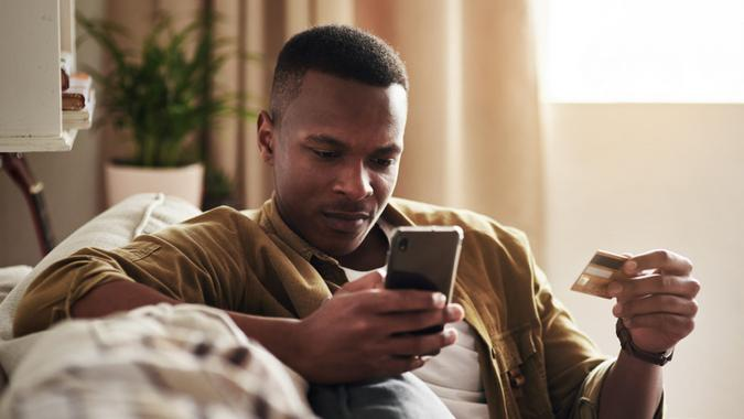 Cropped shot of a handsome young man using a smartphone and a credit card to shop online while sitting on his couch at home.