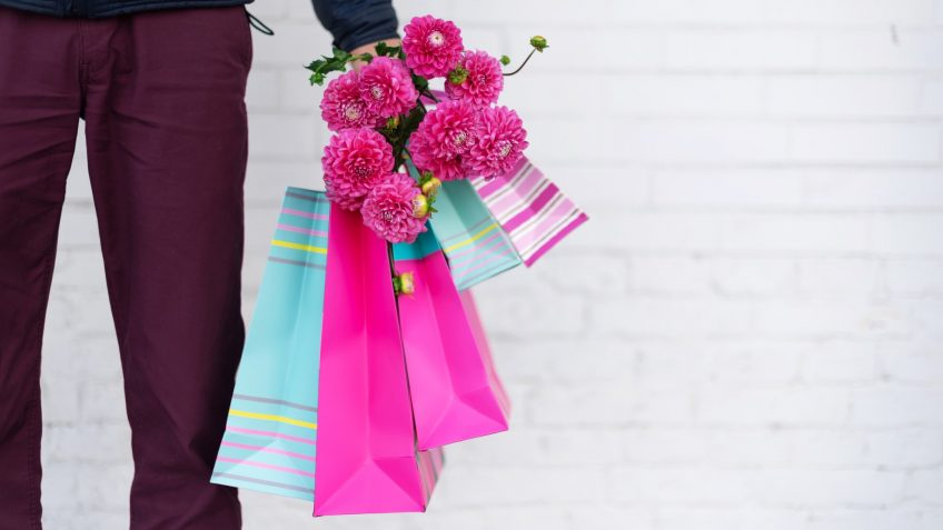 Stylish man holding flowers and pink, blue shopping bags on brick background.