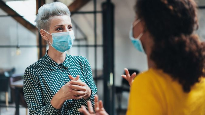 Colleagues businesswomen in the office talking while wearing medical face mask.