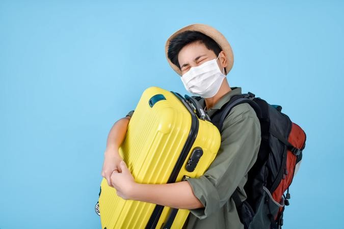 Asian tourists wear masks and carry luggage.