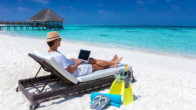 Traveler man sits on a tropical beach with his laptop and works; working in vacation concept.