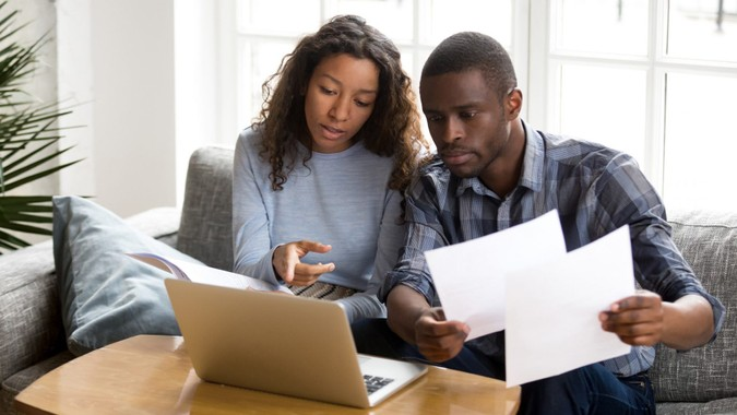 Serious African American couple discussing paper documents, sitting together on couch at home, man and woman checking bills, bank account balance, terms of contract, mortgage, loan agreement.