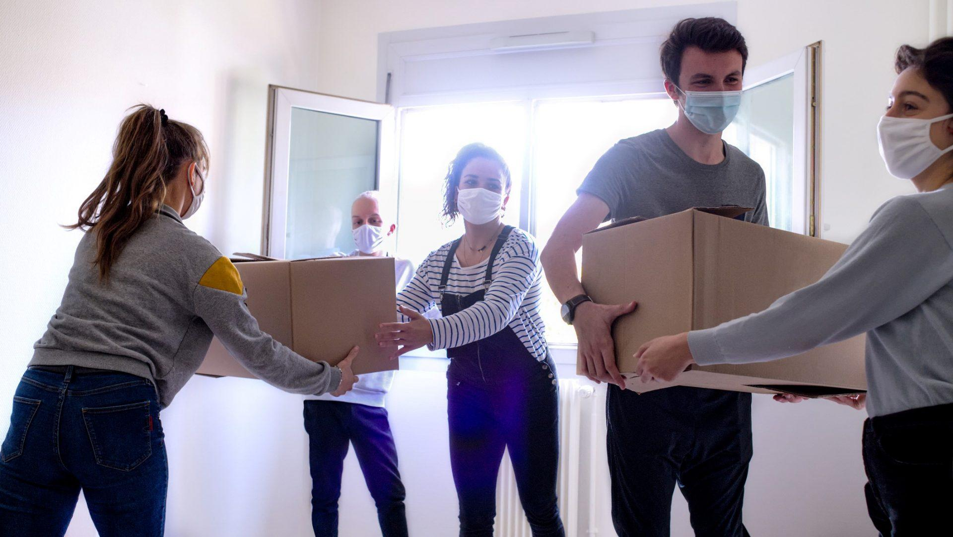 a group of young people carry moving boxes in a room of an apartment.