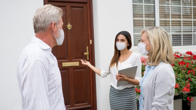 Real estate agent wearing a facemask while showing house to a couple during the COVID-19 pandemic.