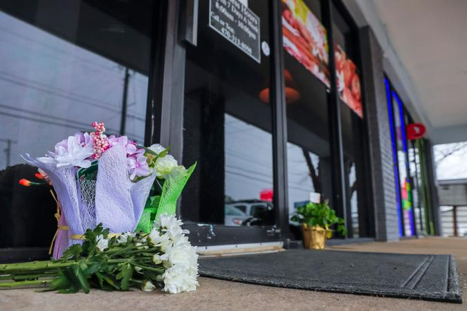 Mandatory Credit: Photo by ERIK S LESSER/EPA-EFE/Shutterstock (11803941e)Flowers left by well-wishers sit at the entrance to Young's Asian Massage spa in Acworth, Georgia, USA, 17 March 2021.