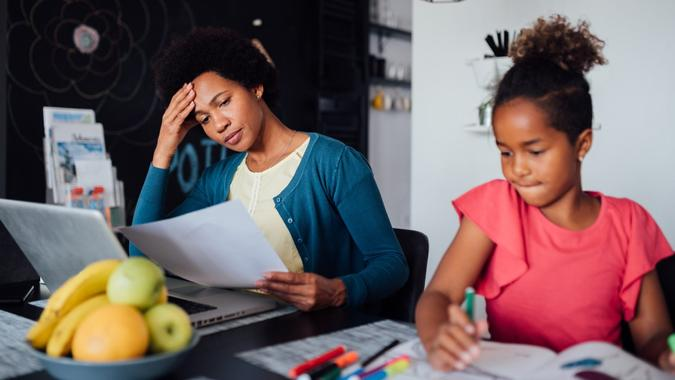 Young African American mother looking for a job using the laptop and struggling while her daughter is being home schooled due to the lack of income.