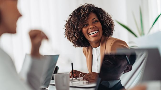 Portrait of cheerful african american businesswoman discussing and smiling at the meeting with colleagues.