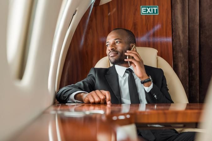 selective focus of handsome african american businessman talking on smartphone in private jet.