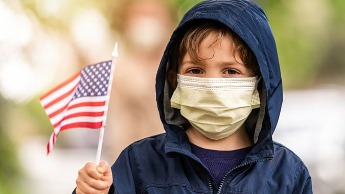 Caucasian Little boy wearing a hooded jacket, a protective mask and holding a US flag.