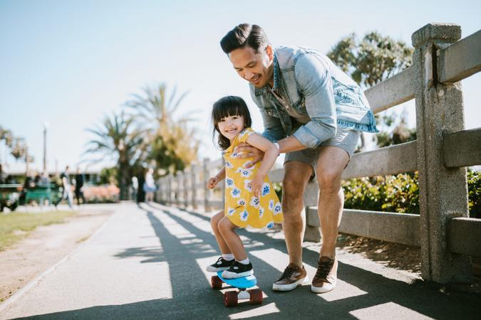A dad helps his little girl go skateboarding, holding her waist for support.