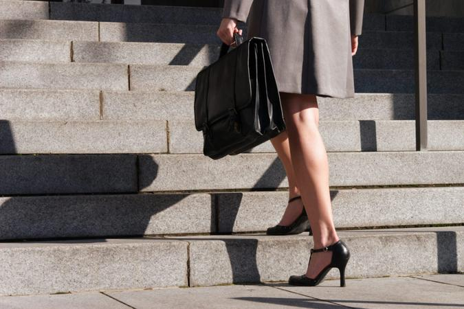A stock image of a business woman ascending stairs holding a briefcase.
