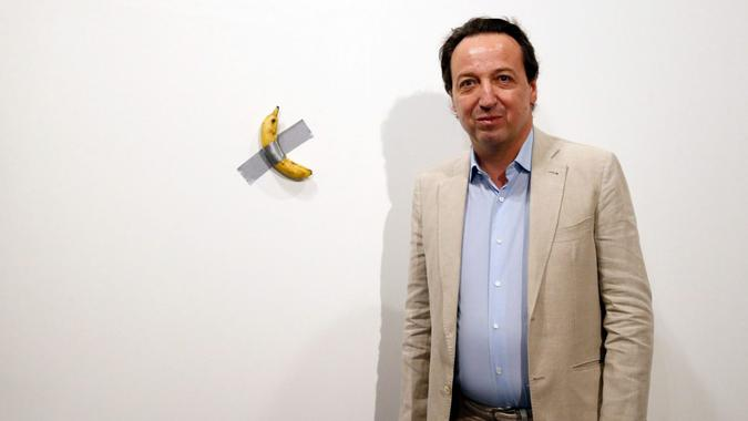 Mandatory Credit: Photo by RHONA WISE/EPA-EFE/Shutterstock (10492891g)Emmanuel Perrotin, founder of the Perrotin Gallery poses with Italian artist Maurizio Cattelan piece's 'Comedian' (a banana duct taped to the wall) during Art Basel in Miami, Florida, USA, 05 December 2019.