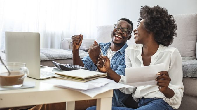 Happy couple with laptop spending time together at home. stock photo