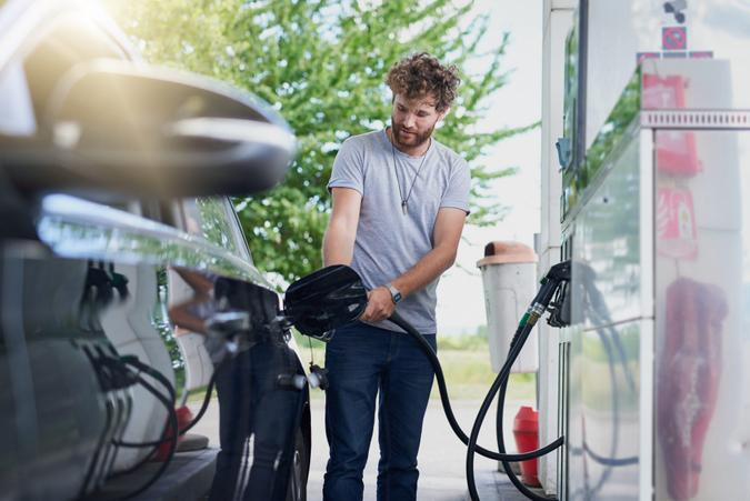 Cropped shot of a handsome young man refuelling his car at a gas station.