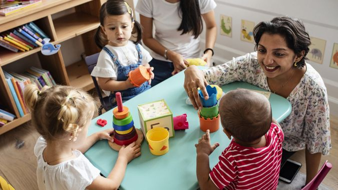 Nursery children playing with teacher in the classroom.