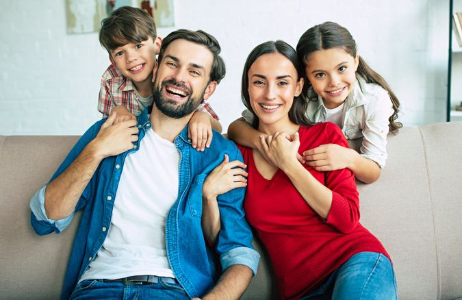 Young happy family relax together at home smiling and hugging.