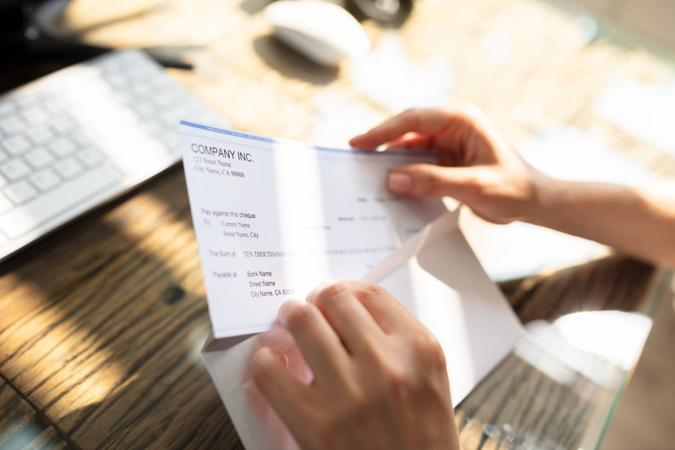 Close-up Of A Businessperson's Hand Opening Envelope With Paycheck Over Wooden Desk.