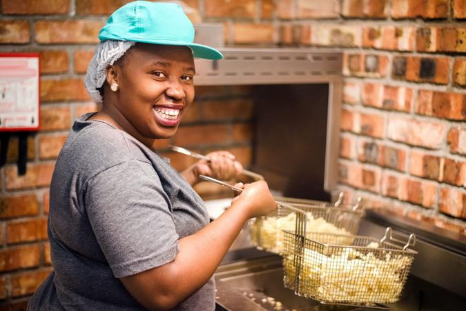 Shot of a smiling female chef cooking french fries at commercial kitchen.