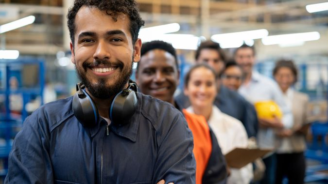 Cheerful handsome blue collar worker and team of engineers at a factory standing in a row smiling at camera with arms crossed.